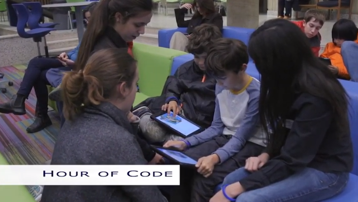students attending Hour of Code sitting on couch with iPad