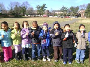elementary students blowing dandelions