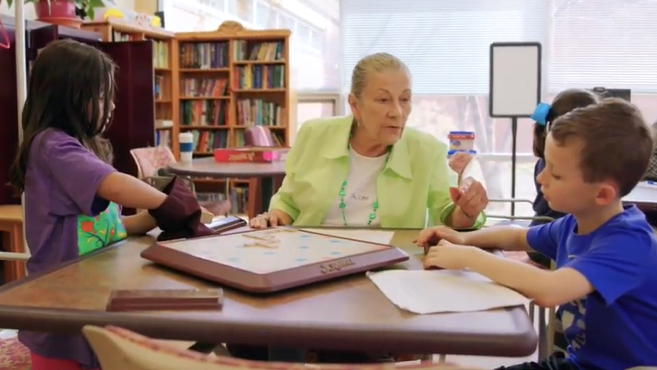 senior citizen playing scrabble with elementary students