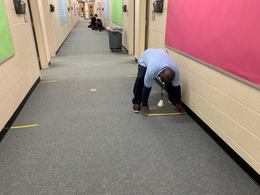staff person marking 6-foot distances on hallway floor