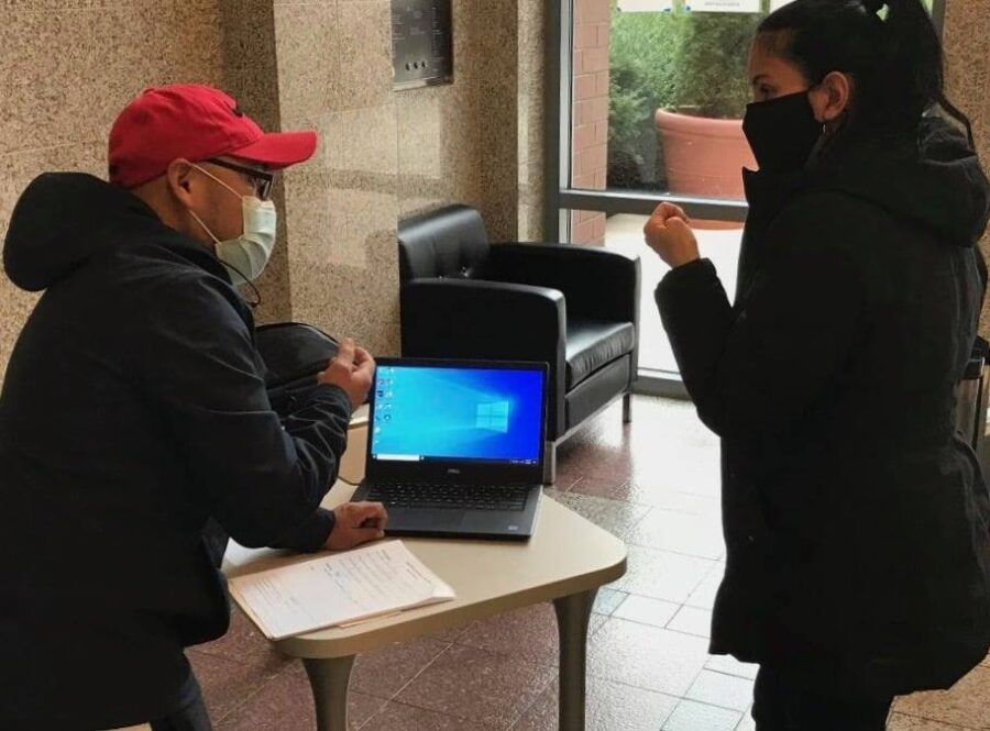 A masked REEP student and a masked technician discuss how to use a loaner laptop to attend online English classes.
