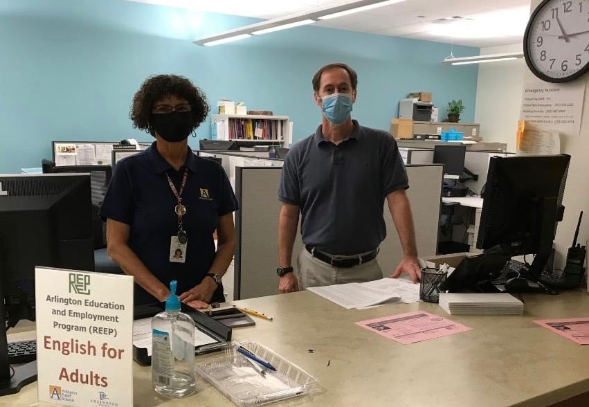 Two REEP staff members are masked and at the welcome counter at Syphax Education Center to help students with registration.