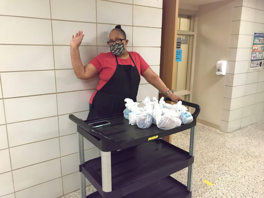 cafeteria staff with bagged breakfasts