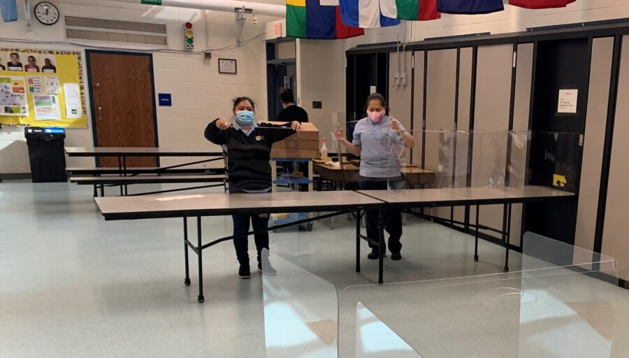 custodians setting up plexiglass shields