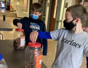Students putting coins into savings jar