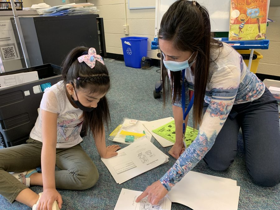 teacher helping student read