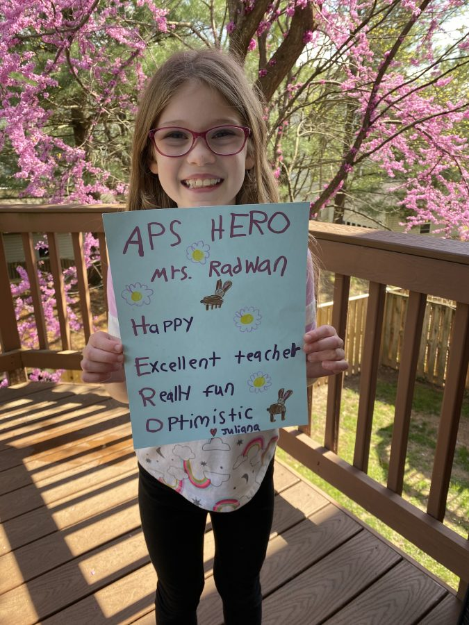student holding a sign thanking an APS Hero