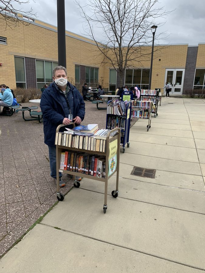 librarian outside with book cart