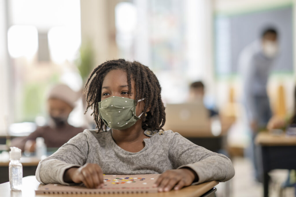 School girl sitting at desk working on a STEM project while wearing a face mask