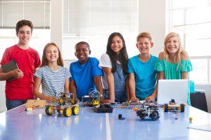 Сургуулийн дараа компьютер кодлох ангид робот машин барьж буй эрэгтэй, эмэгтэй оюутнуудын хөрөг зураг